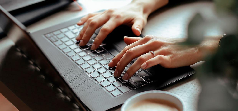 Mãos de uma mulher mexendo no computador