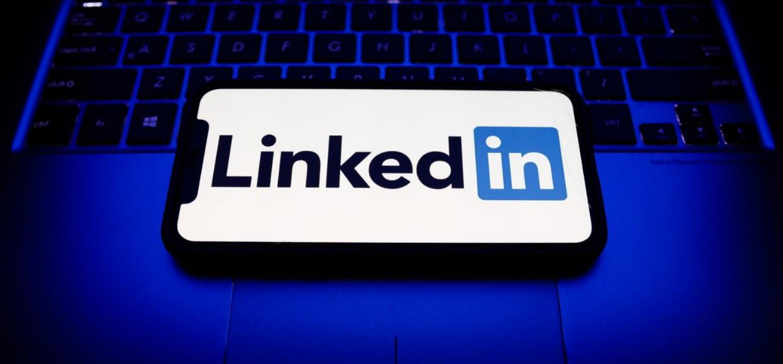 Ambiente escuro com luz apagada, ao centro, um notebook com teclas em efeito neon azul e sobre ele um smartphone com o logotipo do LinkedIn