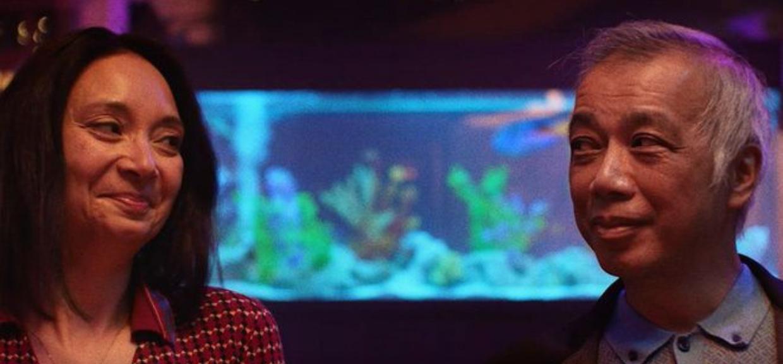Uma mulher e um homem de descendência asiática, com um aquário de fundo. Essa é uma das peças publicitárias da nova campanha do WhatsApp no Brasil.